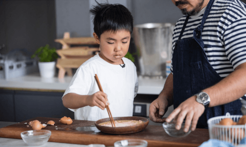 Adam Liaw teaching his son Christopher how to cook