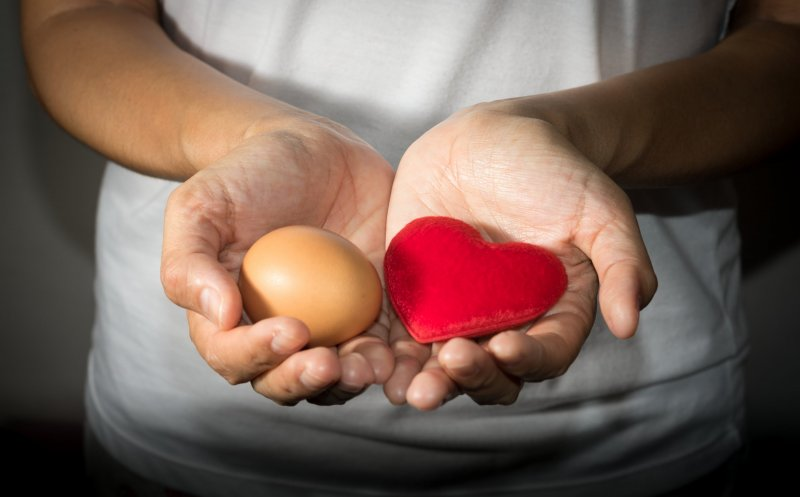 woman holding egg and heart